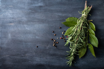 rosemary and laurel leaves  on a dark wooden background