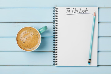 Coffee cup and notebook with to do list on blue rustic desk from above, planning and design concept