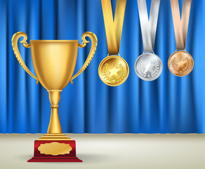 Golden trophy cup and set of medals with ribbons on blue curtain