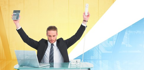 Composite image of businessman cheering holding calculator and telephone