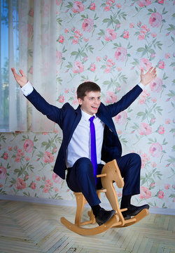Happy childish young man in business suit riding toy wooden horse. Adult acting like a child concept