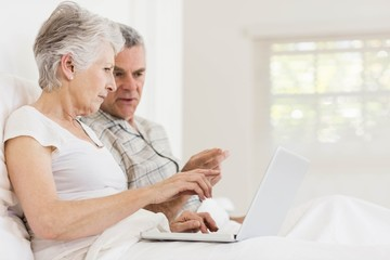 Senior couple using laptop at bed