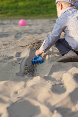 Boy playing in the sand with plastic rake