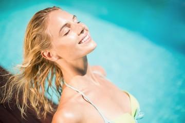 Happy woman in bikini sitting by pool side