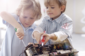 Two little boys disassembling an old radio
