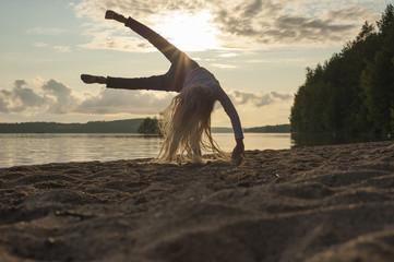 Finland, Karelia, Uukuniemi, little girl turning wheel on the beach at sunset