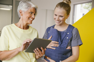 Young mother with baby carrier talking to mature woman with digital tablet in office hallway