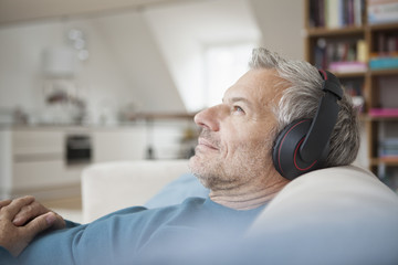 Relaxed man at home wearing headphones listening to music
