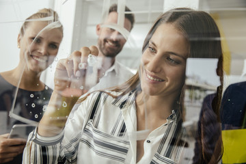 Young woman writing onto glass wall in office