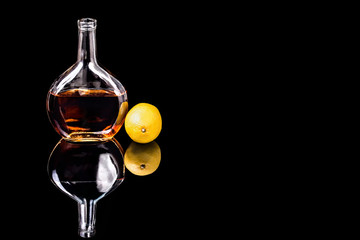 Bottle of Brandy and lemon on the mirror black surface