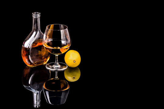 Bottle with Goblet of Brandy and lemon on the mirror black surfa