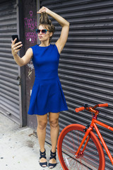Portrait of blond woman wearing blue summer dress taking a selfie with smartphone