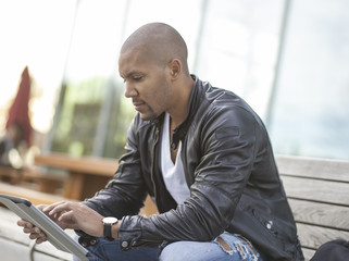 Germany, Cologne, Young man sitting on bench using digital tablet