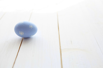 Blue egg on a white old wood table