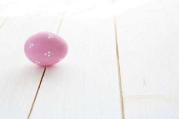 Pink egg on a white old wood table