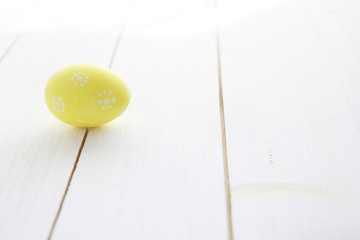 Yellow egg on a white old wood table