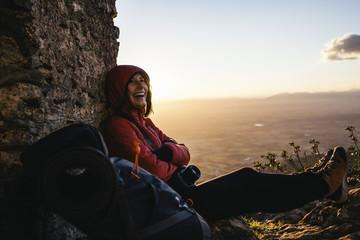 Spain, Catalunya, Girona, happy female hiker resting at stone structure