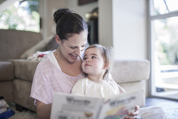 Mother and baby girl at home looking at book