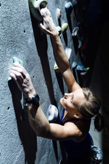 Fit woman rock climbing indoors at the gym.