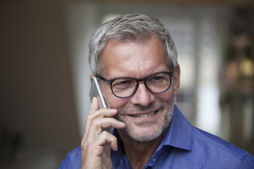 Smiling mature man on cell phone