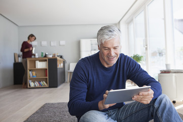 Man sitting on the floor at home using digital tablet