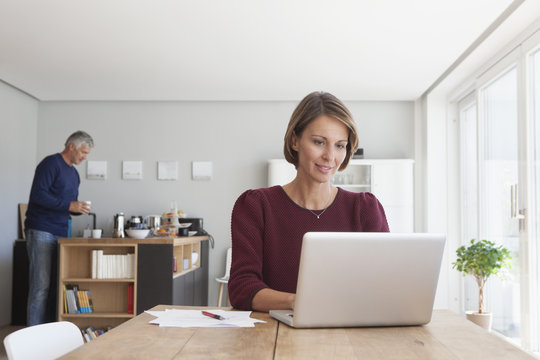 Portrait of woman using laptop at home