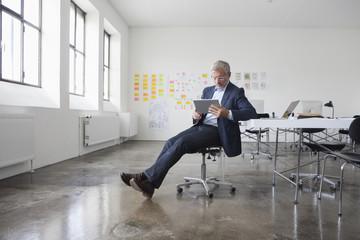 Mature businessman sitting in office using digital tablet