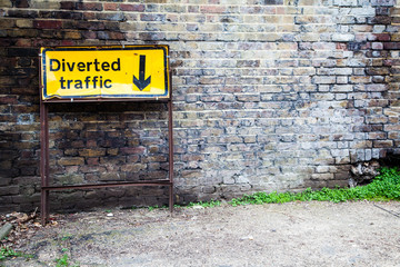 """A sign reading """"Diverted Traffic"""" leans against a wall"""