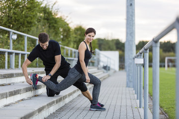 Man assisting woman exercising on sports field