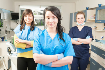 Young smiling assistant in front of her coworker and patient