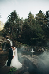Beautiful wedding couple stay on stone of the river in scenic mountains