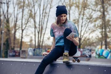 Young woman at skatepark looking at cell phone