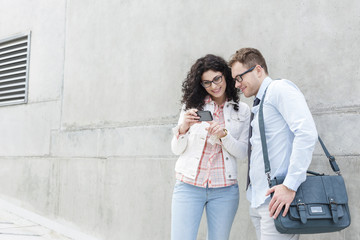 Young man and woman with cell phone outdoors