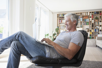 Smiling man relaxing on leather chair at home using laptop