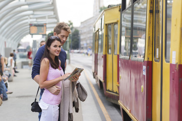 Poland, Warsaw, Young couple at tram stop