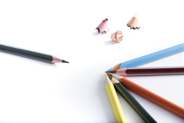 colored pencils on a blank sheet of paper, ready to be used in design