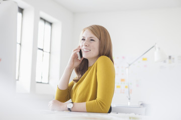 Young woman in office working at desk, using smart phone