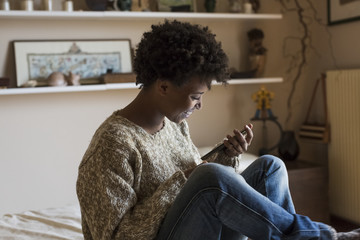 Smiling young woman at home looking at smartphone
