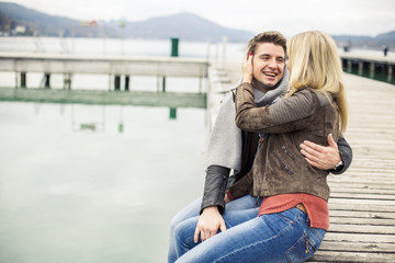 Young couple kissing, sitting on boardwalk, on a lake