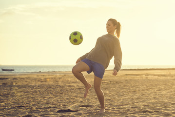 Spain, Young woman playing soccer at the beach