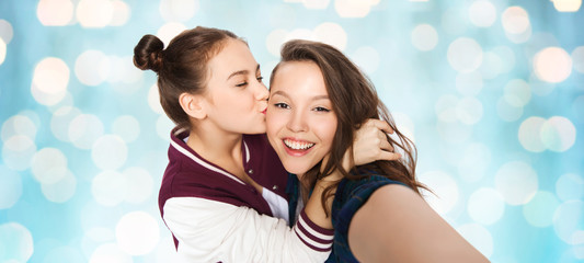 happy teenage girls taking selfie and kissing