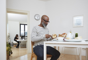 Man having late breakfast at his home office