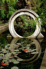 Chengdu, China - May 8, 2008:  A traditional Chinese moon gate reflected in a pond filled with water lilies at the Wen Shu Temple gardens