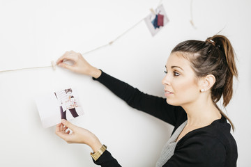 Young woman decorating her home with photos