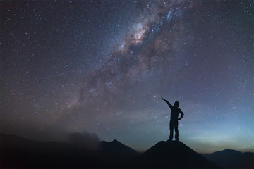 Woman is standing on the hill and pointing the Milky Way.