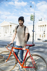 Young man with racing cycle in Vienna, in front of parlament building, Dr.-Karl-Renner-Ring