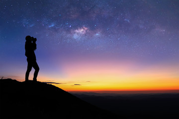 Silhouette of woman is taking the milky way photo on top of mountain