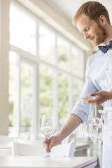 Waiter in restaurant placing wine glasses on dining table