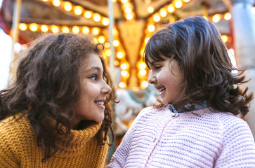 Two little girls face to face in front of a carousel