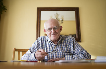 Portrait of smiling senior man with magnifier sitting at a table